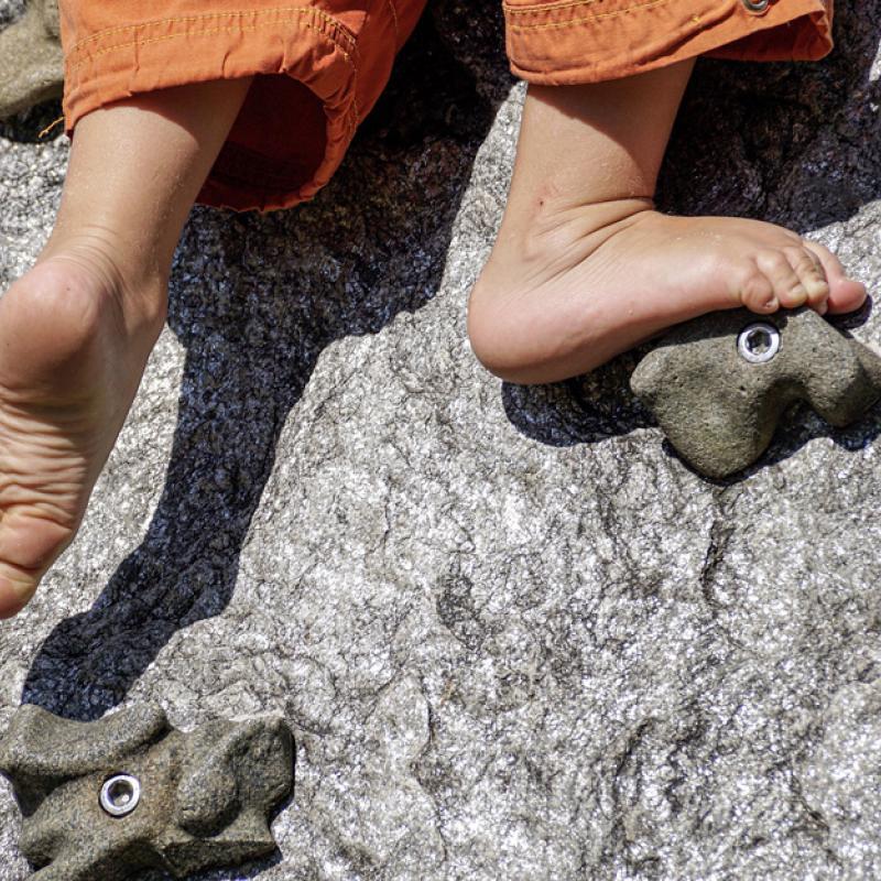 Detailaufnahme von nackten Füßen auf Kletterwand