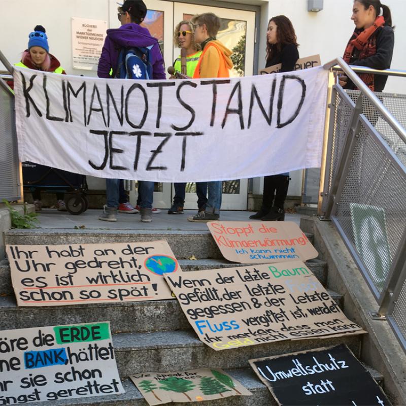 """Transparent """"Klimanotstand"""", dahinter ein paar Jugendliche und viele andere Schilder"""