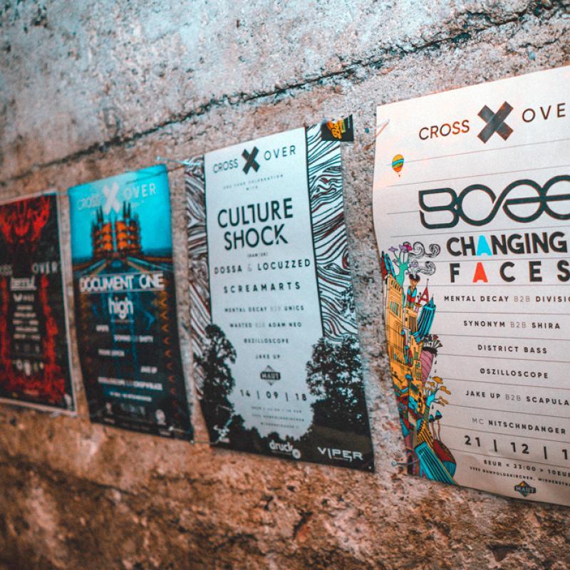 Mauer mit vielen bunten Plakaten darauf