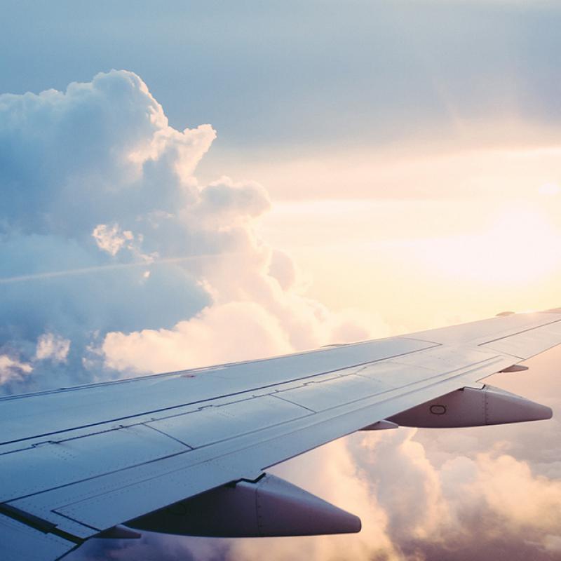 Flügel eines Flugzeuges und Himmel mit Wolken und Sonnenschein