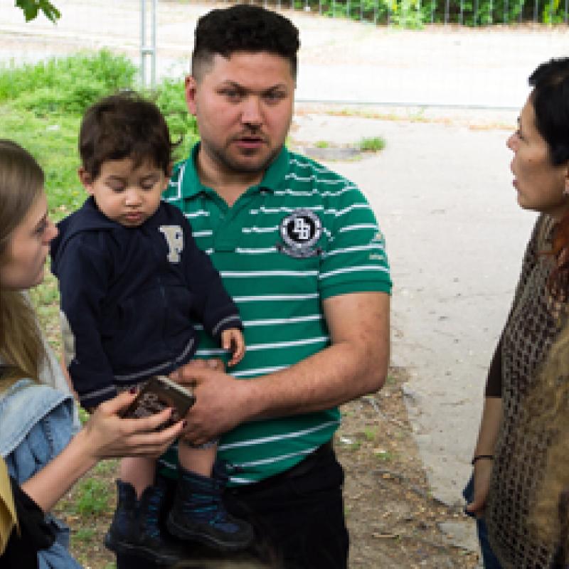 Jugendliche und Flüchtling mit Kind im Garten