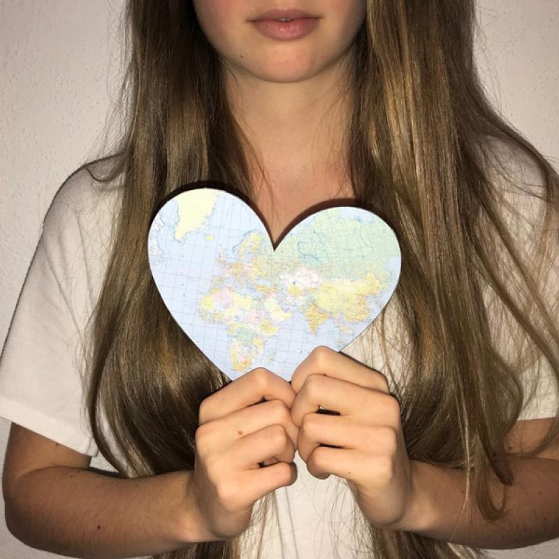 Mädchen mit ausgeschnittenem Herz aus einer Landkarte