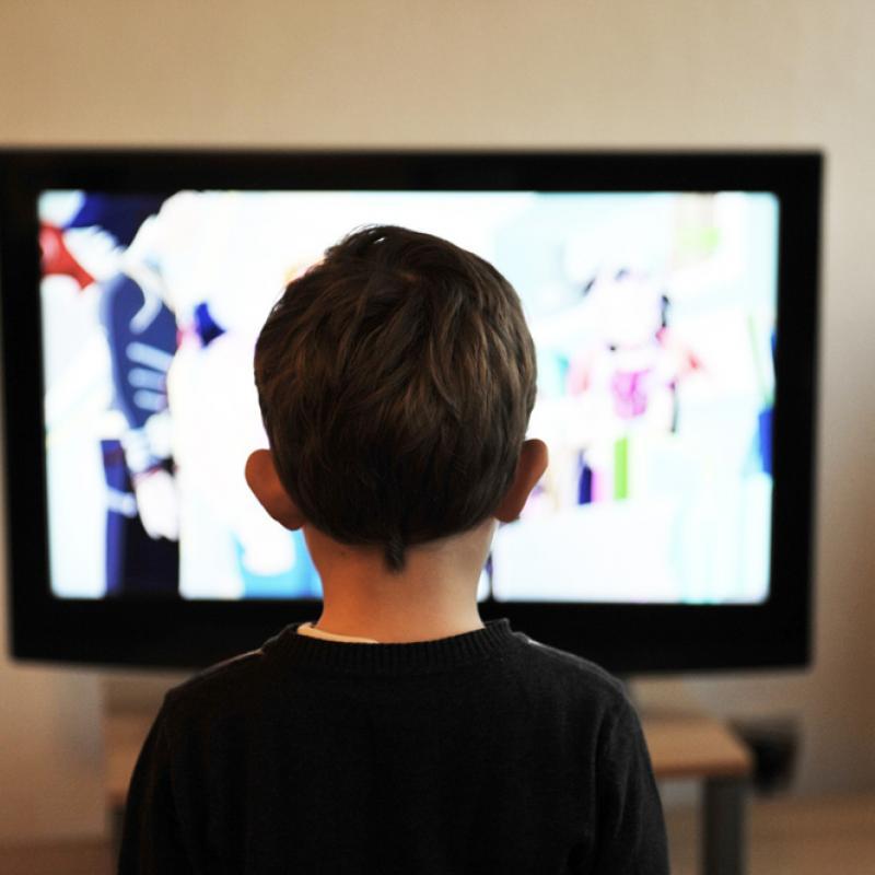 Kind von hinten, das vor einem Fernseher sitzt.