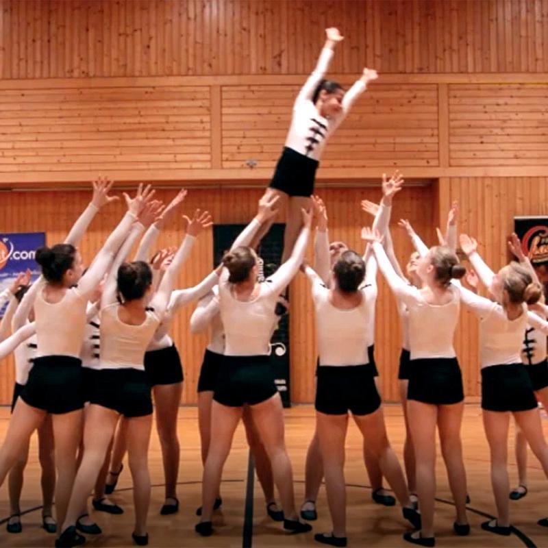 Gruppe von Turnerinnen in Aktion - ein Mädchen wird in die Luft geworfen