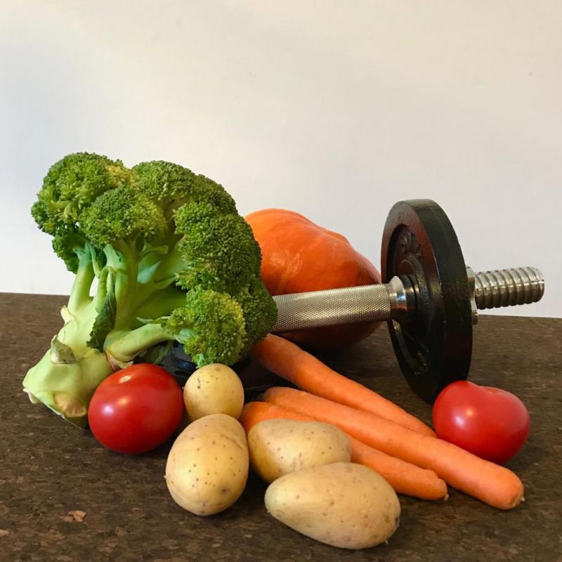 Hantel liegt mit Gemüse auf einem Tisch