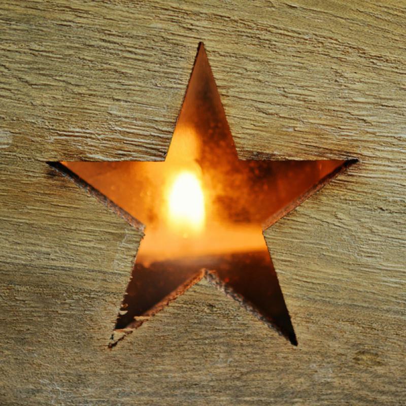 Holzbrett mit ausgeschnittenem Stern und dahinter eine Kerze