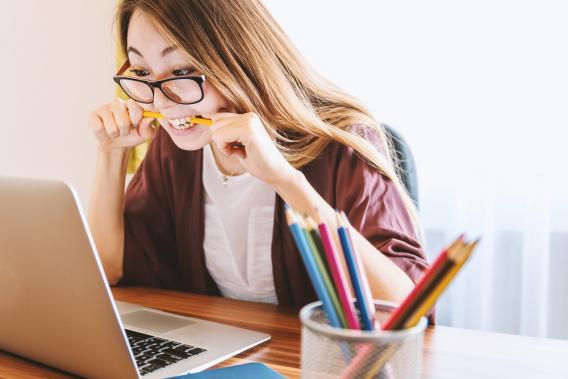 Mädchen sitzt vorm Laptop und kaut auf einem Bleistift rum