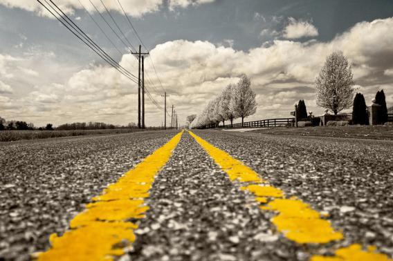 Straße mit gelber Linie, dahinter Horizont mit Wolken