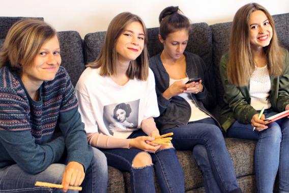 4 Jugendliche sitzen auf der Couch und lachen in die Kamera