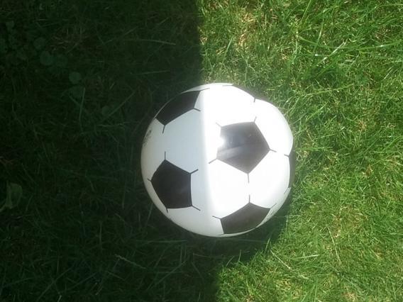 Fußball auf einer Wiese - die halbe Seite im Schatten