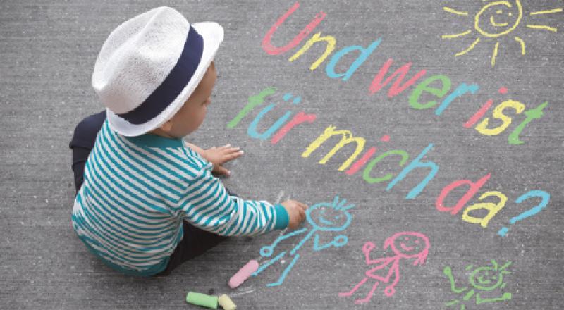 Kleines Kind malt mit Kreide auf einer Straße