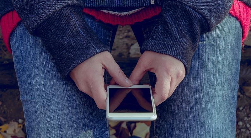 Hände im Schoß mit Handy