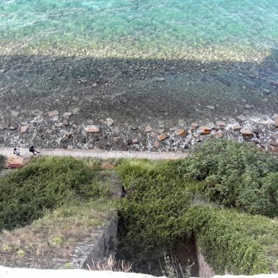 Blick von oben auf einen Wanderweg am Meer entlang