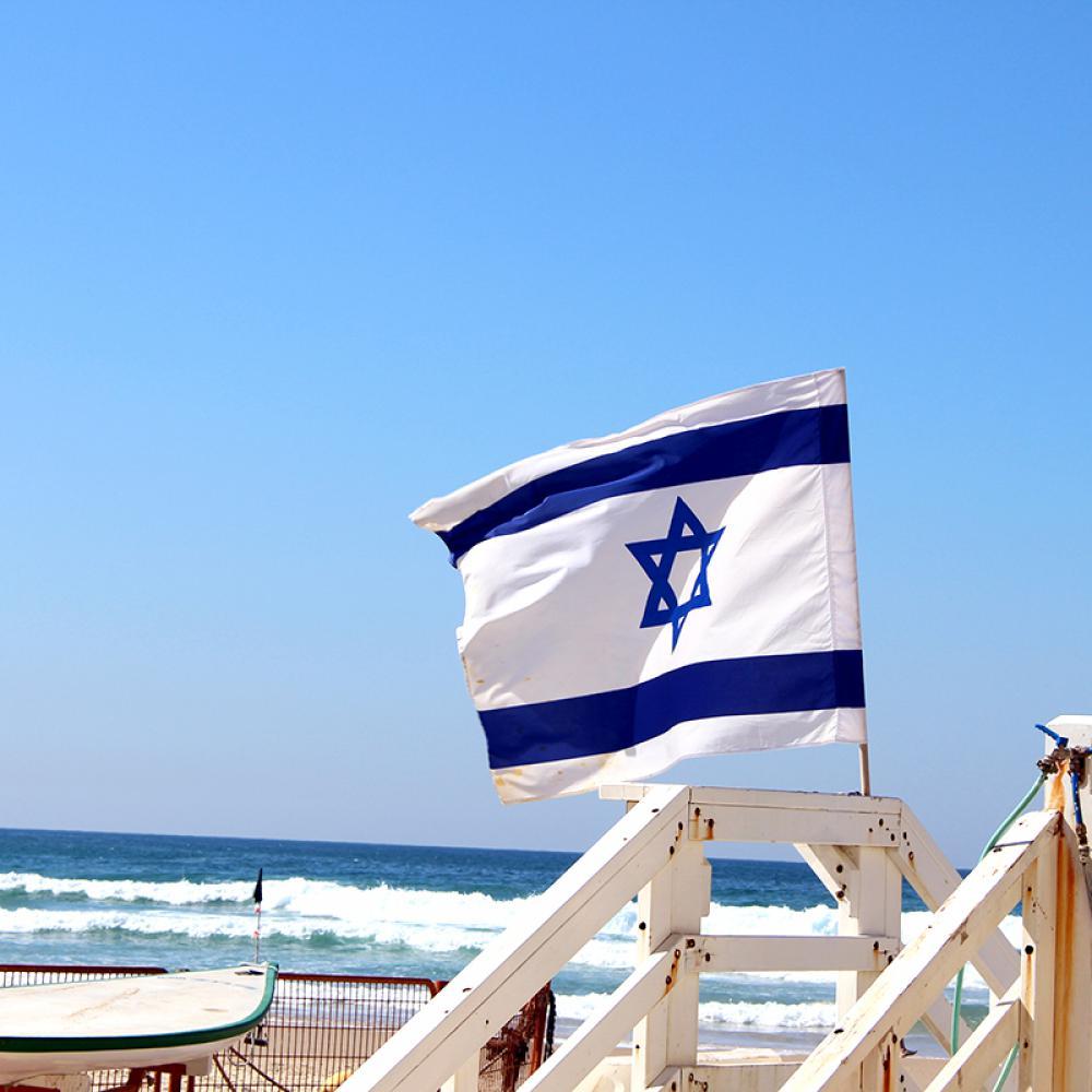 Israel-Fahne weht im Wind, dahinter Strand und Meer von Tel Aviv