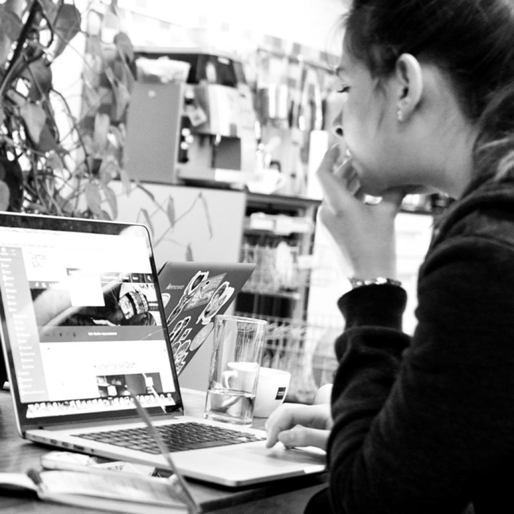 Mädchen sitzt vor Laptop und schreibt